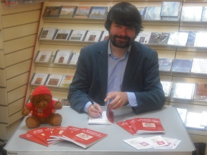The author signing signing copies of the book (with the help of 'St Tedmund')